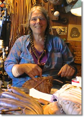 Photo of Fran Fleet in her shop. Fran does baseball glove repair and is the developer of Glove Stuff&#174 baseball glove conditioner